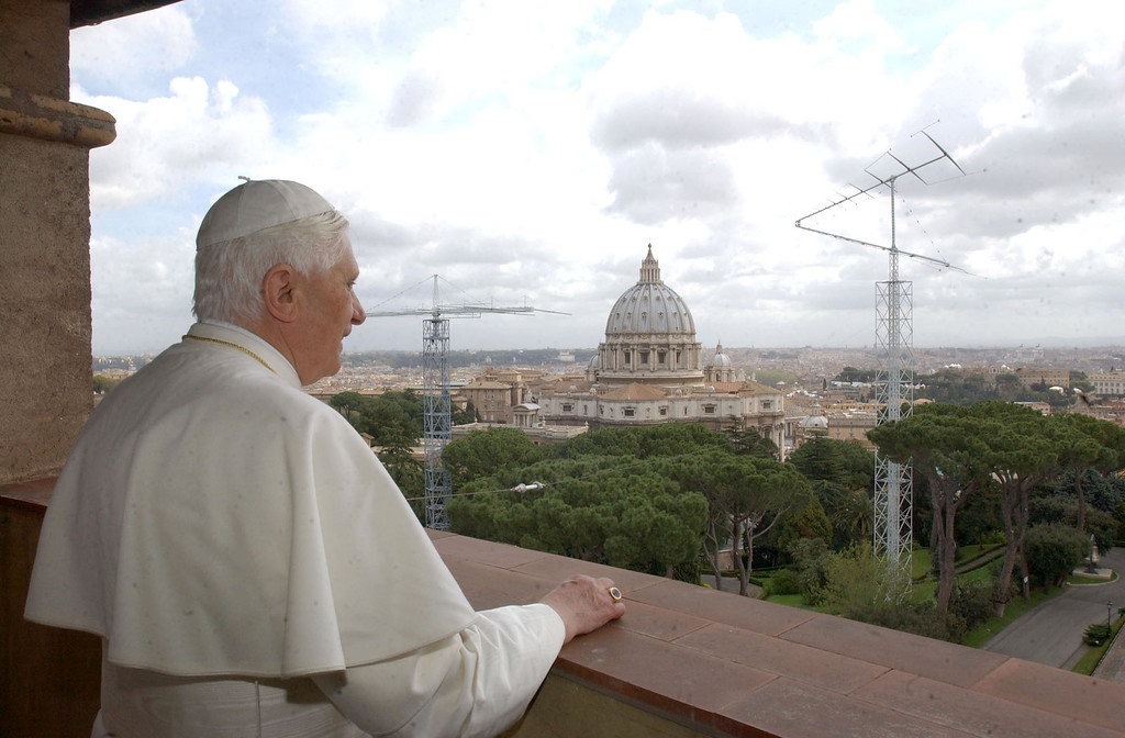 . Pope Benedict XVI stands looking outside his new apartment with St. Peter\'s Basilica in the background April 20, 2005 in Vatican City. Cardinal Ratzinger was elected the new Pope on April 19.  (Photo by Arturo Mari-Pool/Getty Images)