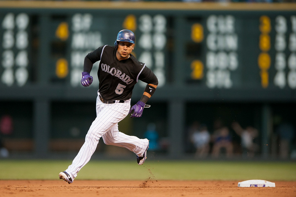 . DENVER, CO - AUGUST 06:  Carlos Gonzalez #5 of the Colorado Rockies rounds second base to score a run in the fourth inning of a game against the Chicago Cubs at Coors Field on August 6, 2014 in Denver, Colorado.  (Photo by Dustin Bradford/Getty Images)