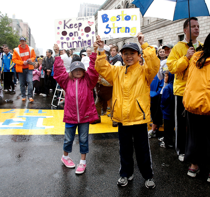 . Maxwell Surprenant, right, and Emily Perron hold up signs cheering on runners who were unable to finish the Boston Marathon on April 15 because of the bombings after the city allowed them to finish the last mile of the race in Boston, Saturday, May 25, 2013. (AP Photo/Winslow Townson)