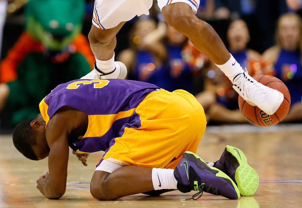 . ORLANDO, FL - MARCH 20:  DJ Evans #3 of the Albany Great Danes is kneed in the head unintentionally by a Florida Gators players in the second half during the second round of the 2014 NCAA Men\'s Basketball Tournament at Amway Center on March 20, 2014 in Orlando, Florida.  (Photo by Kevin C. Cox/Getty Images)