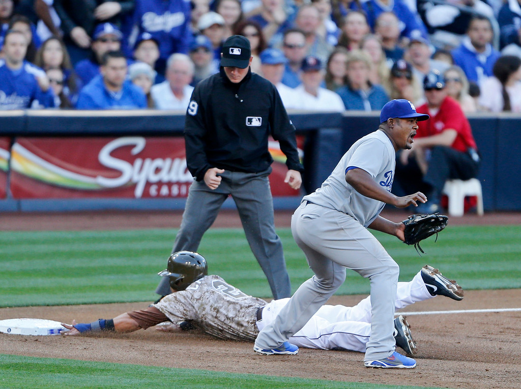 . San Diego Padres\' Everth Cabrera slides into third safely as Los Angeles Dodgers third baseman Juan Uribe awaits a late throw in the first inning of the opening game of Major League baseball in the United States Sunday, March 30, 2014, in San Diego.  (AP Photo/Lenny Ignelzi)