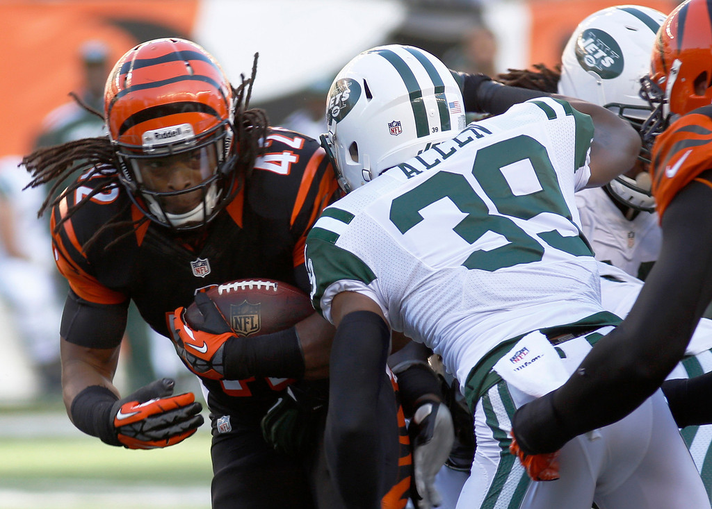 . Cincinnati Bengals running back BenJarvus Green-Ellis (42) is tackled by New York Jets free safety Antonio Allen (39) in the first half of an NFL football game, Sunday, Oct. 27, 2013, in Cincinnati. (AP Photo/David Kohl)