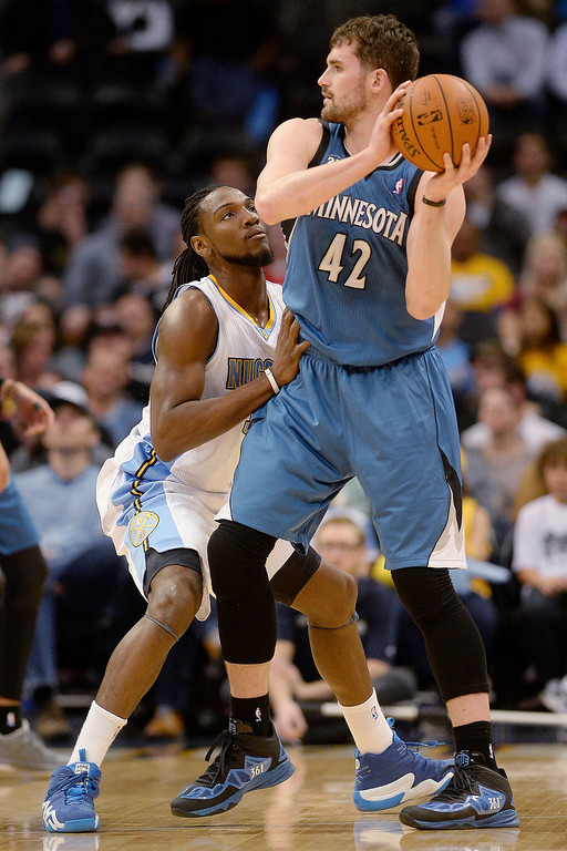 . Kenneth Faried (35) of the Denver Nuggets defends Kevin Love (42) of the Minnesota Timberwolves during the first quarter at the Pepsi Center. (Photo By AAron Ontiveroz/The Denver Post)