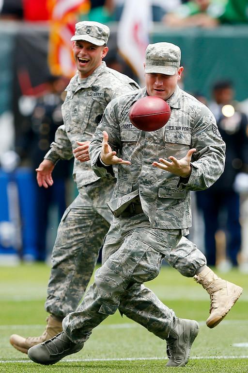 . Members of the military go for a pass thrown by Philadelphia Eagles long snapper Jon Dorenbos during NFL football training camp Monday, July 28, 2014, in Philadelphia. (AP Photo/Matt Rourke)