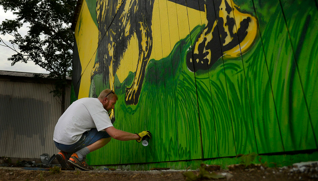 . Jon Lamb (pictured) and Michael Ortiz of Like Minded Productions work on a large mural outside of the Herbal Cure. The Mural that faces I-25 near the Washington St. and Emerson Street exit was photographed on Tuesday, July 15, 2014. (Photo by AAron Ontiveroz/The Denver Post)