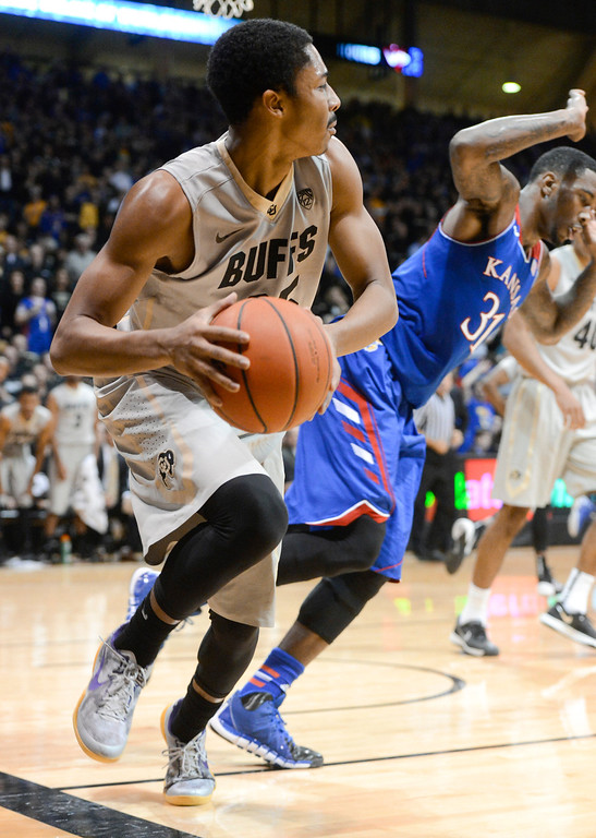 . Colorado University point guard, Spencer Dinwiddie, left, grabs a rebound against Kansas forward, Jamari Traylor, right, in the first half of play at the Coors Events Center in Boulder Colorado Saturday afternoon, December 07, 2013. (Photo By Andy Cross/The Denver Post)
