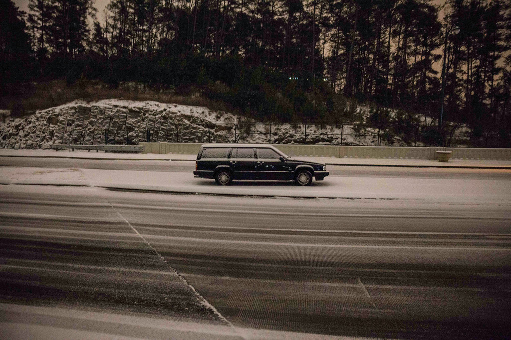 . A car sits abandoned on Peachtree Center Parkway, Tuesday evening, Jan. 28, 2014, in Dunwoody, Ga. Around Atlanta, nearly all public entities and most businesses were shut down early Wednesday, and officials encouraged would-be motorists not to drive. (AP Photo/Branden Camp)