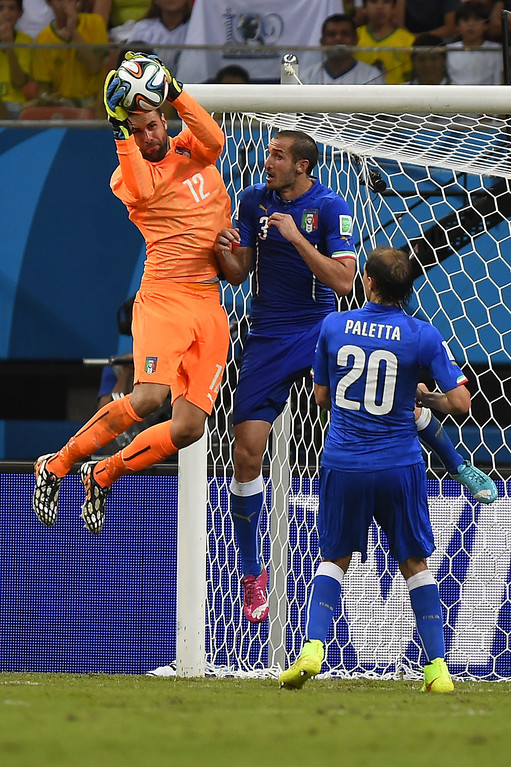 . Italy\'s goalkeeper Salvatore Sirigu (L) saves the ball as Italy\'s defender Giorgio Chiellini (C) and Italy\'s defender Gabriel Paletta watch on during a Group D football match between England and Italy at the Amazonia Arena in Manaus during the 2014 FIFA World Cup on June 14, 2014. AFP PHOTO / FABRICE COFFRINI