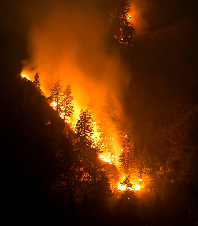 . Fire creeps slowing down the western canyon wall above the Wood River in Hailey where firefighters continue to battle the Beaver Creek Fire Saturday Aug. 17, 2013. (AP Photo/Idaho Statesman, Darin Oswald)