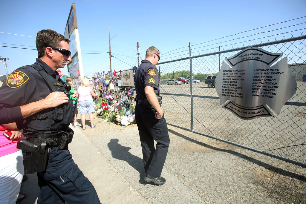 . Prescott police officers look at a plaque with names of the 19 fallen firefighters outside of Granite Mountain Hotshots Fire Station 7 in Prescott, Arizona July 2, 2013.  AFP PHOTO / KRISTA  Kennell/AFP/Getty Images