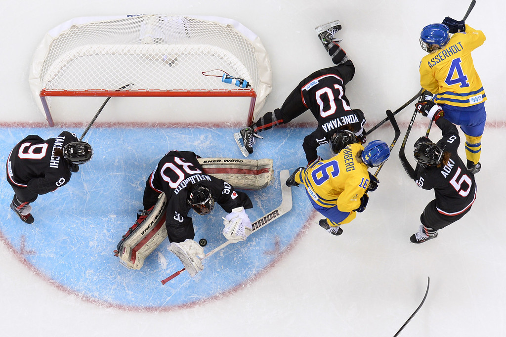 . Sweden\'s Jenni Asserholt (R) and Sweden\'s Pernilla Winberg (C) fight for the puck with Japan\'s goalkeeper Nana Fujimoto (2ndL), Japan\'s Kanae Aoki (R) and Japan\'s Haruna Yoneyama (top C) during the Women\'s Ice Hockey Group B match Sweden vs Japan at the Shayba Arena during the Sochi Winter Olympics on February 9, 2014. ANDREJ ISAKOVIC/AFP/Getty Images