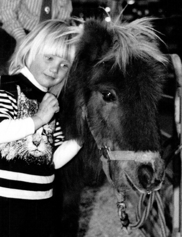 . Ariel Wheeler, 4, of Boulder, snuggles up against a Shetland pony in Ranchland in the Hall of Education at the National Western Stock Show.  1989. Denver Post Library photo archive