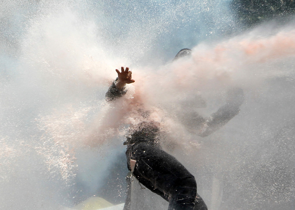 . A protester tries to remain standing as police water cannon fires water during clashes at the Taksim Square in Istanbul Tuesday, June 11, 2013.  (AP Photo/Thanassis Stavrakis)