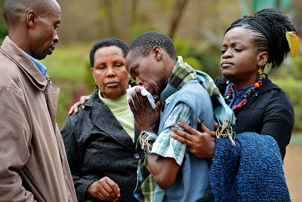 . A man only identified by his first name, Stephen (C) is comforted by Pastor Elizabeth Akinyi (R) and family members at the city mortuary in Nairobi on September 23, 2013. Stephen\'s father was killed in the Westgate mall siege on September 21, 2013. AFP PHOTO/Carl de  SOUZA/AFP/Getty Images