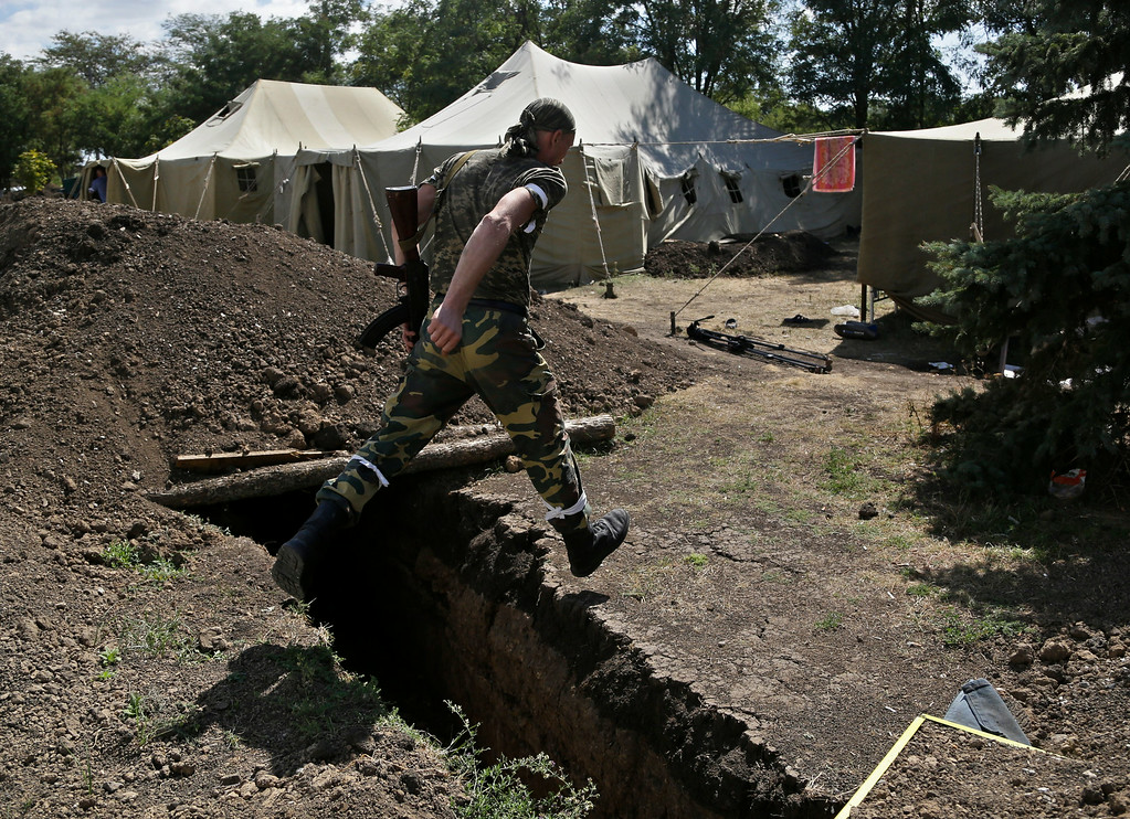 . A Pro-Russian rebel jumps over the trench at the Novoazovsk border crossing point,in eastern Ukraine, Friday, Aug. 29, 2014. In Novoazovsk, pro Russian rebel fighters looked to be in firm control, well-equipped and relaxed. At least half a dozen tanks were seen on roads around the town, although the total number at the rebelsí disposal is believed to be much greater. Novoazovsk fell swiftly to the rebels Wednesday after being pounded by shelling.(AP Photo/Sergei Grits)