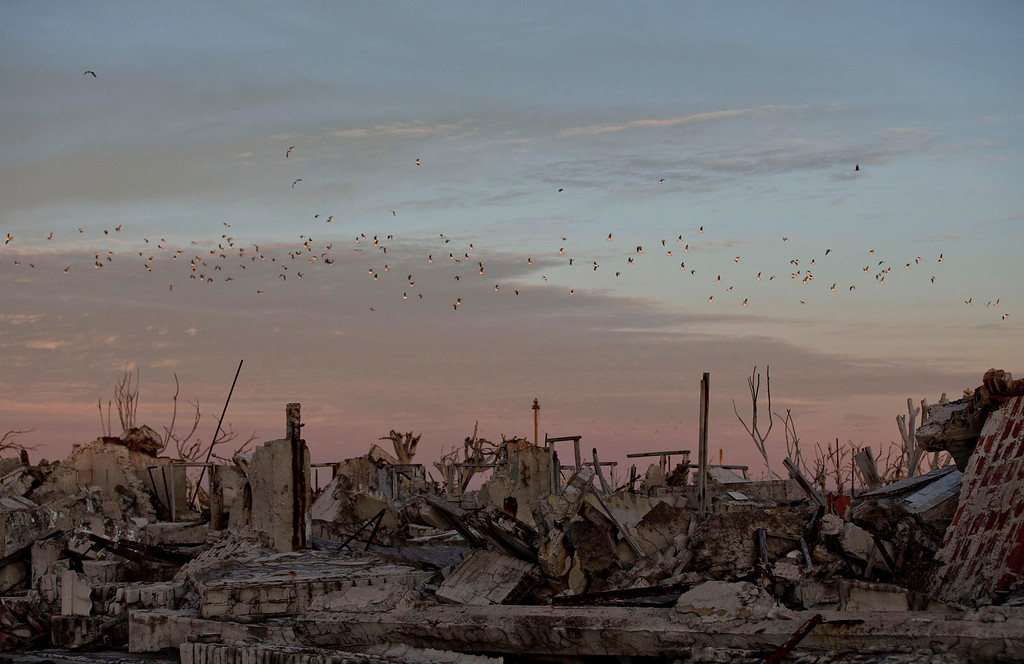 . In this May 7, 2013 photo, birds fly over the village of Epecuen, Argentina. Epecuen village was once home to 1,500 residents before it started flooding on November 10, 1985. After heavy rains the lake Epecuen burst its banks . It only took 20 days for  the town to submerge beneath almost 10 metres (30 feet) of water forcing everybody to leave. As the years passed slowly the water started to recede. Nowadays the town that was never rebuilt, and was famous for therapeutic salty waters that surrounded it, is once again becoming a tourist destination but for the ruins that have been left. (AP Photo/Natacha Pisarenko)