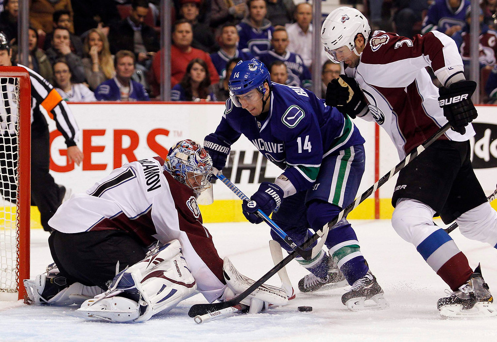 . Vancouver Canucks\' Alexandre Burrows (C) is stopped by Colorado Avalanche goaltender Semyon Varlamov (L) and Ryan O\'Byrne (R) during the first period of their NHL hockey game in Vancouver, British Columbia January 30, 2013.   REUTERS/Ben Nelms