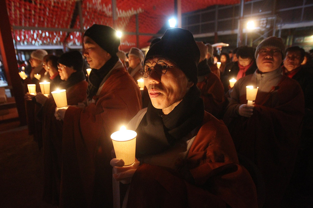 . Buddhist monks hold candle lights during New Year\'s Eve celebrations at Bongeun Buddhist temple in Seoul, South Korea, Wednesday, Jan. 1, 2014. (AP Photo/Ahn Young-joon)