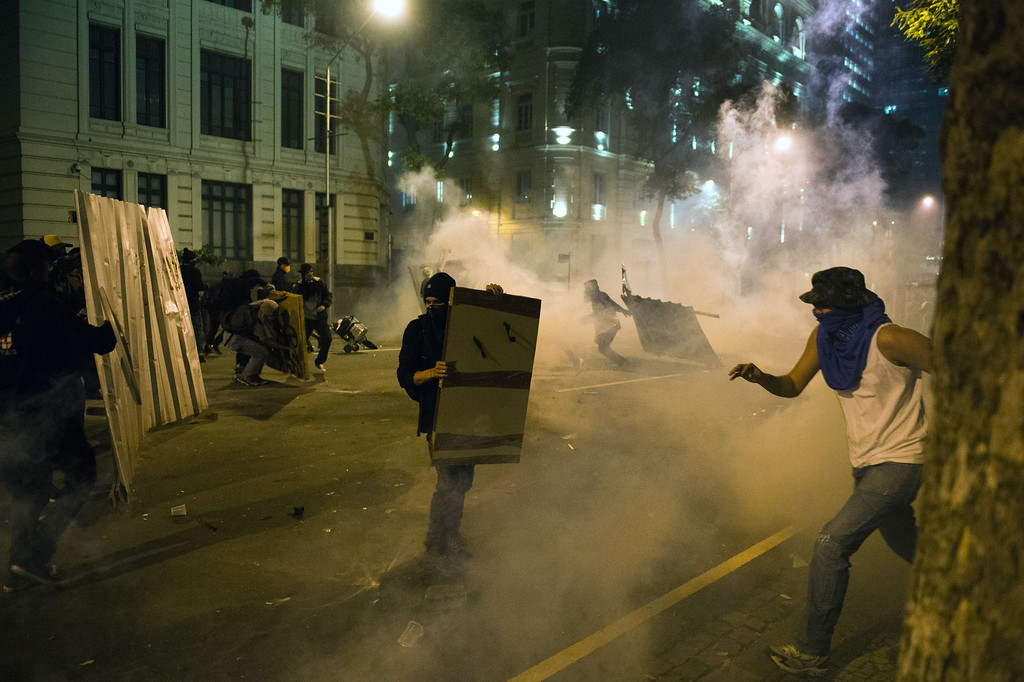 """. Demonstrators clash with police after a protest for the \""""Teachers\' day\"""", on October 15, 2013 in Rio de Janeiro, Brazil. AFP PHOTO / CHRISTOPHE SIMON/AFP/Getty Images"""