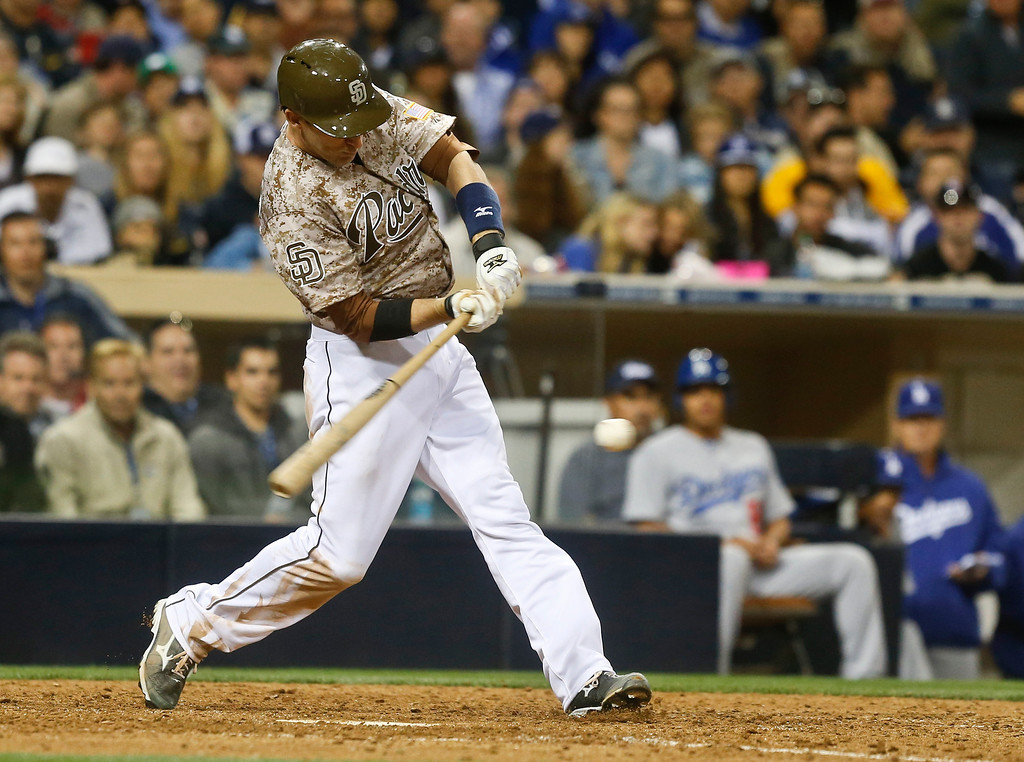 . San Diego Padres\' Chris Denorfia connects for a two run single against the Los Angeles Dodgers in the eighth inning of the opening game of Major League baseball in the United States Sunday, March 30, 2014, in San Diego.  (AP Photo/Lenny Ignelzi)
