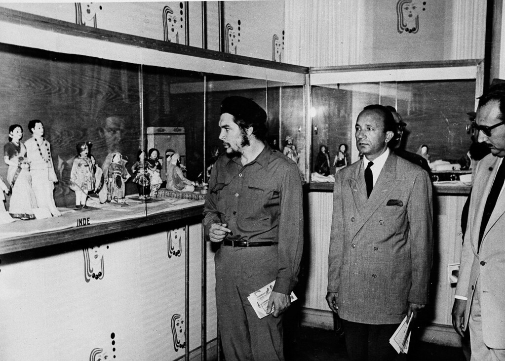 """. Commander Ernesto \""""Che\"""" Guevara, Cuban President Fidel Castro\'s right hand man, looks at the permanent doll exhibition at Ras-El-Tin Palace, Alexandria, Egypt, June 20, 1959.  At center is Alexandria\'s Governor Ismail Mehanna.  Man at far right is unidentified.  (AP Photo/Abdel Latif)"""