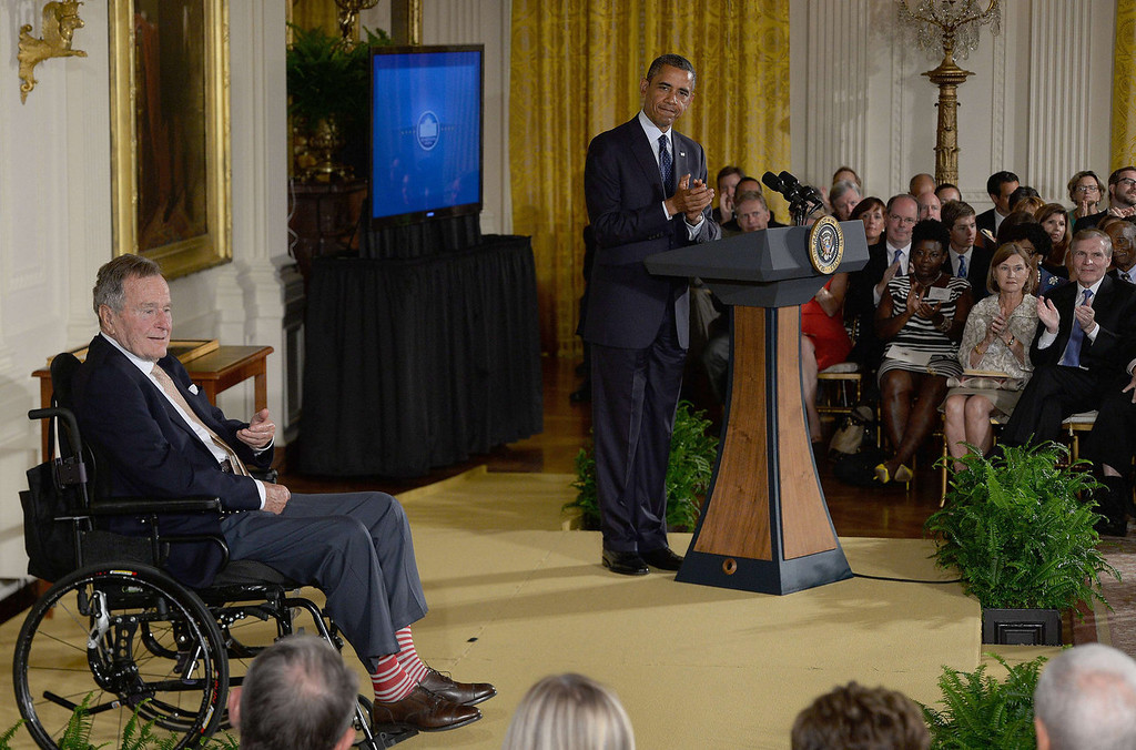 . US President Barack Obama applauds as former US President George H.W. Bush (L) attends a White House ceremony to recognize the Points of Light volunteer program in Washington, DC, July 15, 2013.  President Obama and First Lady Michelle Obama hosted former President George H.W. Bush and former first lady Barbara Bush to honor the 5,000th Daily Points of Light Award winner.  JIM WATSON/AFP/Getty Images