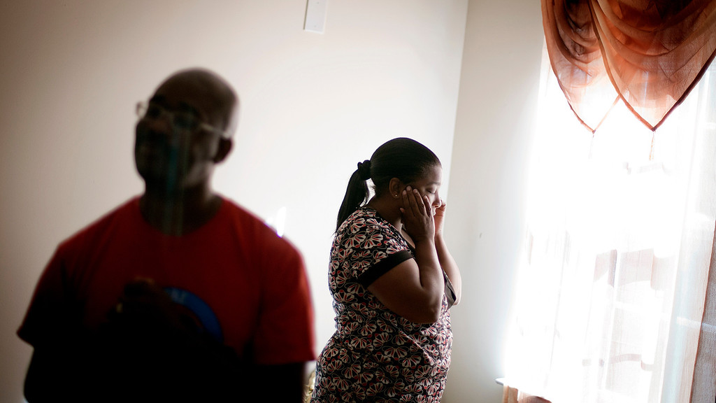 """. Tiawanna Burnette, center, stands in the living room with her husband, Jimmie Burnette, who lost his vision to a brain tumor in 2010, at their home in Atlanta on May 27, 2012. \""""I was seeing how my visual impairment changed my wife. It made her have to pick up the slack and do things. I never wanted my wife to work hard or take on a task that\'s something that I\'m supposed to be doing.\"""" (AP Photo/David Goldman)"""