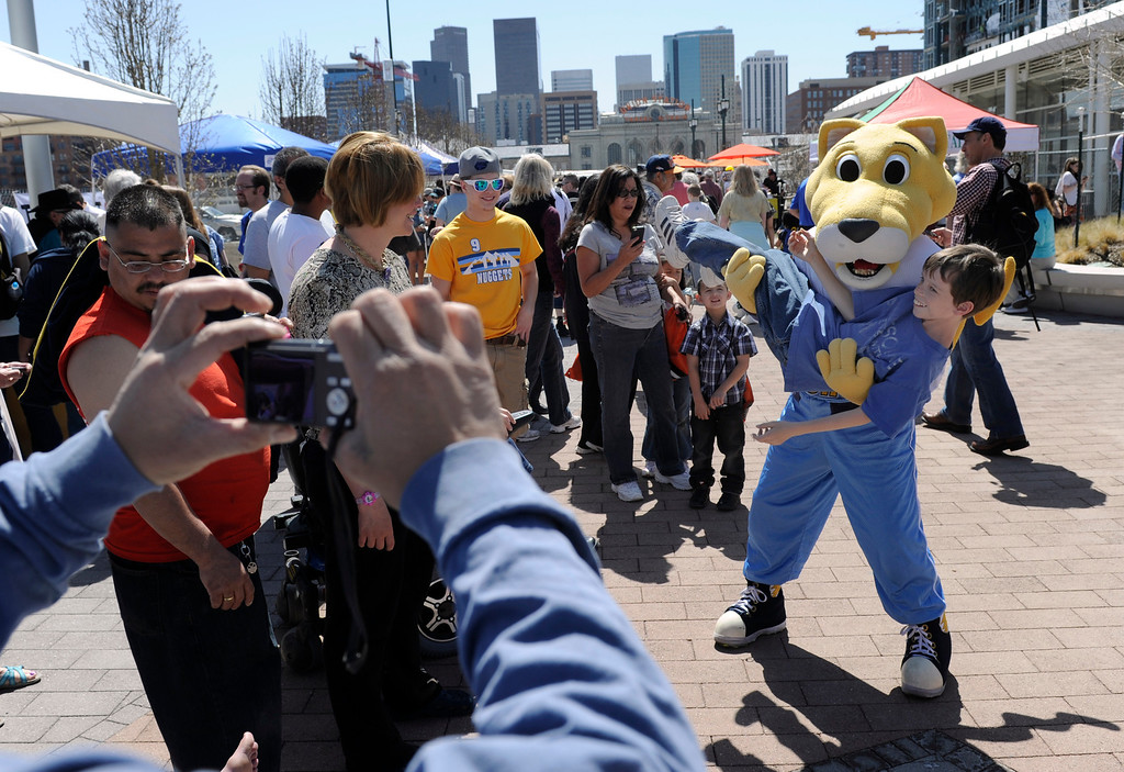 ". DENVER, CO.- APRIL 27: Zach Spear, 11, from Colorado Springs, gets a lift from ""Rocky\"", the Denver Nuggets team mascot. RTD celebrates the opening of the West line of the light rail with free rides for all and a party atmosphere at many of the stops along the route. Union station had Denver sports team mascots making the rounds as well as live music and food. (Photo By Kathryn Scott Osler/The Denver Post)"