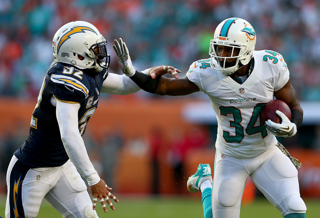 . Marcus Thigpen #34 of the Miami Dolphins tries to block Eric Weddle #32 of the San Diego Chargers during their game at Sun Life Stadium on November 17, 2013 in Miami Gardens, Florida.  (Photo by Streeter Lecka/Getty Images)