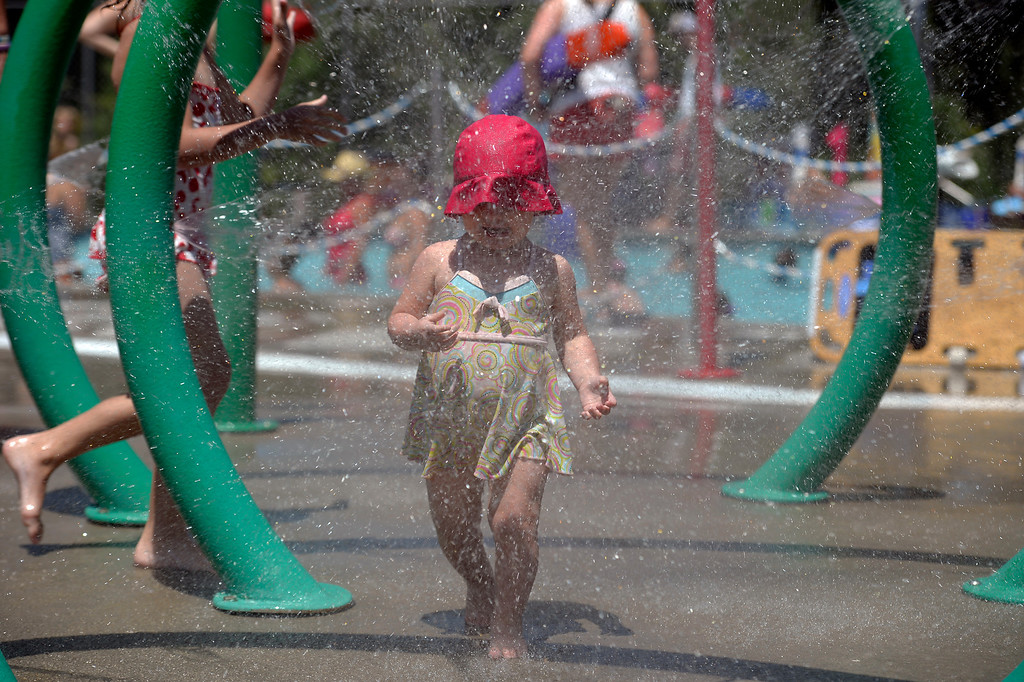 . Rylie Michna 1 year 7 mos, walks through the water mister to cool off at Pirates Cove July 16, 2013. (Photo By John Leyba/The Denver Post)