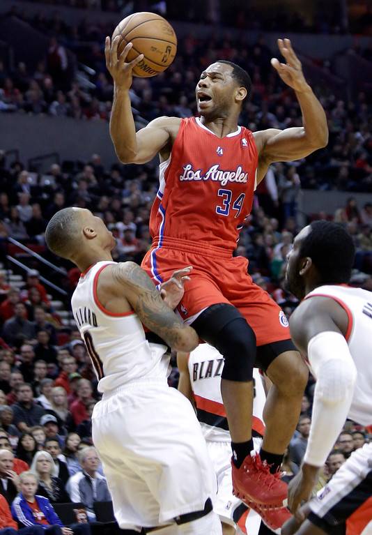 . Los Angeles Clippers guard Willie Green, middle, goes up for a shot between the Portland Trail Blazers Damian Lillard, left, and J.J. Hickson during the first quarter of an NBA basketball game in Portland, Ore., Saturday, Jan. 26, 2013.(AP Photo/Don Ryan)