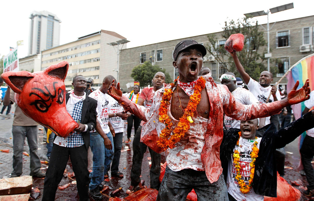 . A protestor smeared with animal blood reacts as he participates in a demonstration against lawmakers\' demands for a pay rise, outside parliament buildings in Nairobi, June 11, 2013. Refusing to accept a cut imposed by the Salaries and Remuneration Commission in May, members of parliament voted to increase their salaries to 130 times the minimum wage, which according to them, are needed to deter bribery and provide charitable support for constituents. Protesters have deemed the proposed salary raise a violation of the constitution, according to news reports. REUTERS/Thomas Mukoya