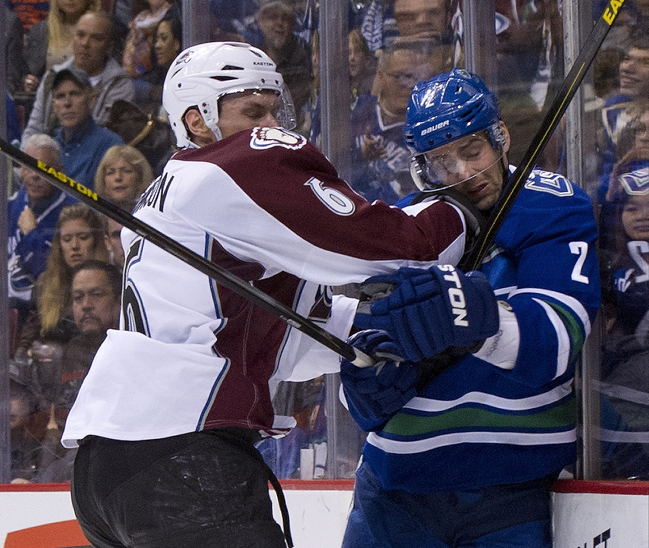 . Erik Johnson #6 of the Colorado Avalanche delivers a hit to Dan Hamhuis #2 of the Vancouver Canucks behind the net during the second period in NHL action on March 28, 2013 at Rogers Arena in Vancouver, British Columbia, Canada.  (Photo by Rich Lam/Getty Images)