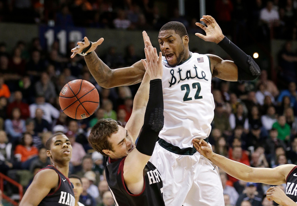 . Michigan State\'s Branden Dawson (22) and Harvard\'s Laurent Rivard go for a loose ball in the second half during the third round of the NCAA men\'s college basketball tournament in Spokane, Wash., Saturday, March 22, 2014. Michigan State won 80-73. (AP Photo/Elaine Thompson)