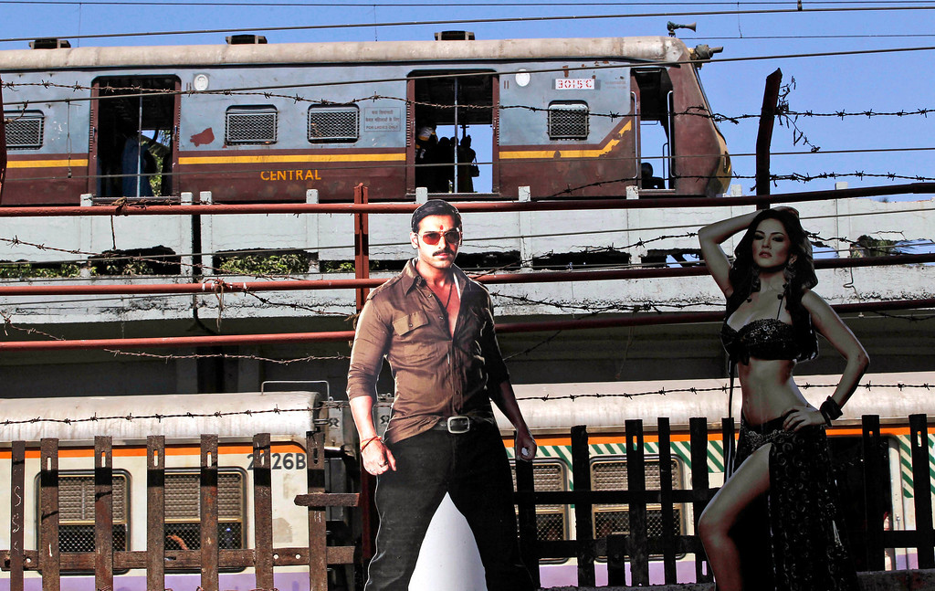 ". A train moves past cutouts of Bollywood actors John Abraham and Sunny Leone displayed outside a cinema hall in Mumbai, India, Friday, May 3, 2013. Four top Indian filmmakers have come together to make ""Bombay Talkies,\"" a short-film collection that hits theaters Friday to celebrate 100 years of Indian cinema. India\'s first full-length feature film \""Raja Harishchandra,\"" or \""King Harishchandra,\"" was released in 1913. Since then Indian cinema has become the largest producer of films in the world. India produced nearly 1,500 films last year, according to accounting firm KPMG. (AP Photo/Rajanish Kakade)"