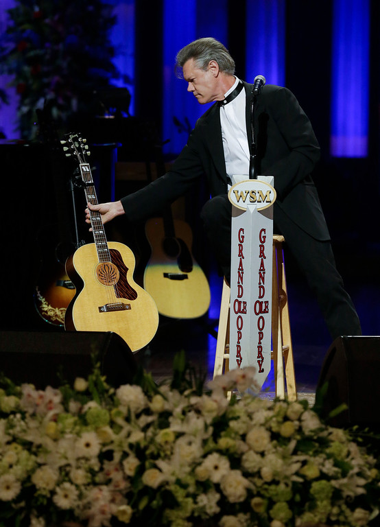 . Randy Travis sets down his guitar after performing during the funeral for country music star George Jones in the Grand Ole Opry House on Thursday, May 2, 2013, in Nashville, Tenn.  (AP Photo/Mark Humphrey, Pool)