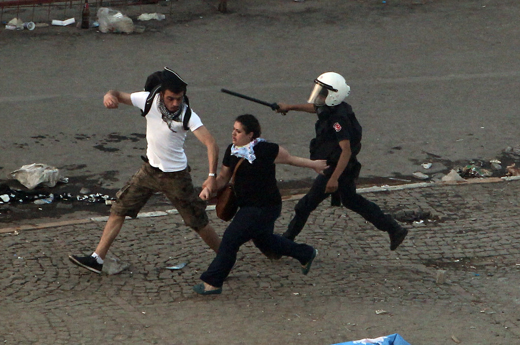 . A couple of protesters run to avoid a policeman during clashes at the Taksim Square in Istanbul Tuesday, June 11, 2013.  (AP Photo/Thanassis Stavrakis)