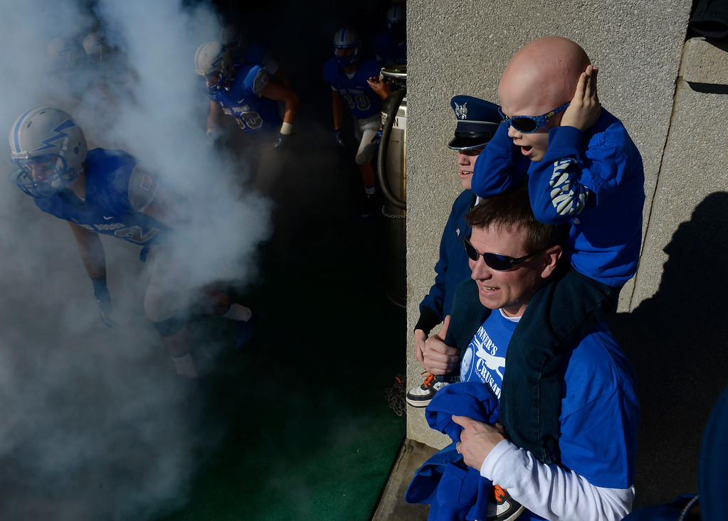 . COLORADO SPRINGS, CO - OCTOBER 26: Conner Arnold, 5, covers his ears while on his dad\'s shoulders, Air Force Major, Eric Arnold, while Conner\'s brother, Air Force cadet. Christian Arnold, watches his team, the Air Force Falcons, take the field to play Notre Dame at Falcon Stadium Saturday afternoon, October 26, 2013. Conner is battling Ewings Sarcoma cancer an had a chance to get a first-hand look at his favorite team Saturday afternoon. (Photo By Andy Cross/The Denver Post)