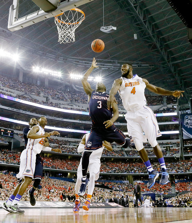 . Connecticut guard Terrence Samuel (3) shoots as Florida center Patric Young (4) defends during the first half of the NCAA Final Four tournament college basketball semifinal game Saturday, April 5, 2014, in Arlington, Texas. (AP Photo/David J. Phillip)