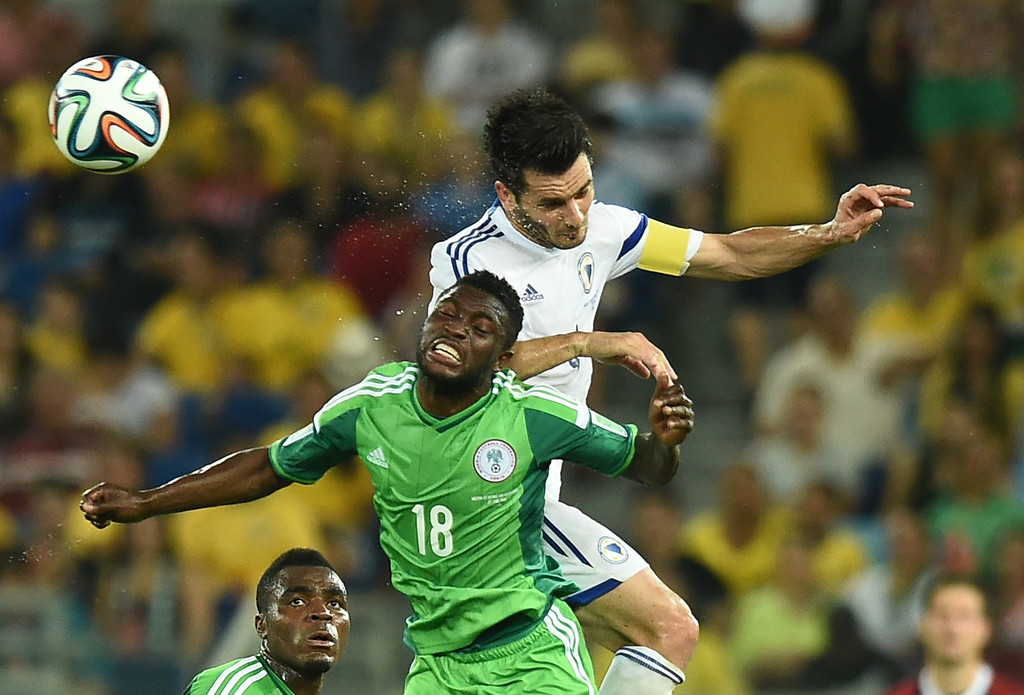 . Nigeria\'s forward Michael Babatunde jumps to head the ball with Bosnia-Hercegovina\'s defender and captain Emir Spahic (back) during the Group F football match between Nigeria and Bosnia-Hercegovina at the Pantanal Arena in Cuiaba during the 2014 FIFA World Cup on June 21, 2014. JEWEL SAMAD/AFP/Getty Images