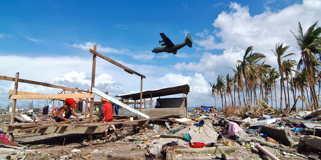 . A military C130 plane passes by a shanty being rebuilt following the recent super typhoon on November 21, 2013 in Tacloban,  Leyte, Philippines.  (Photo by Dondi Tawatao/Getty Images)