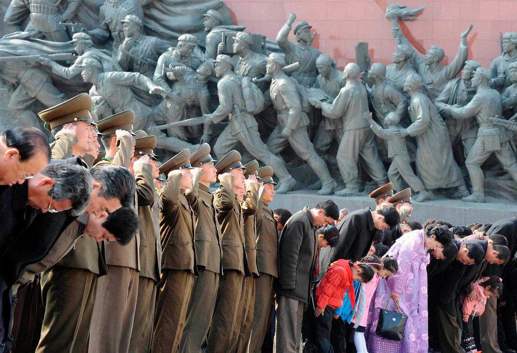 . North Korean soldiers salute as civilians bow to bronze statues (not pictured) of North Korea\'s late founder Kim Il-sung and late leader Kim Jong-il at Mansudae in Pyongyang, in this photo taken and provided by Kyodo on April 15, 2013, on the 101st birthday of North Korean founder Kim Il-sung. Mandatory Credit. REUTERS/Kyodo