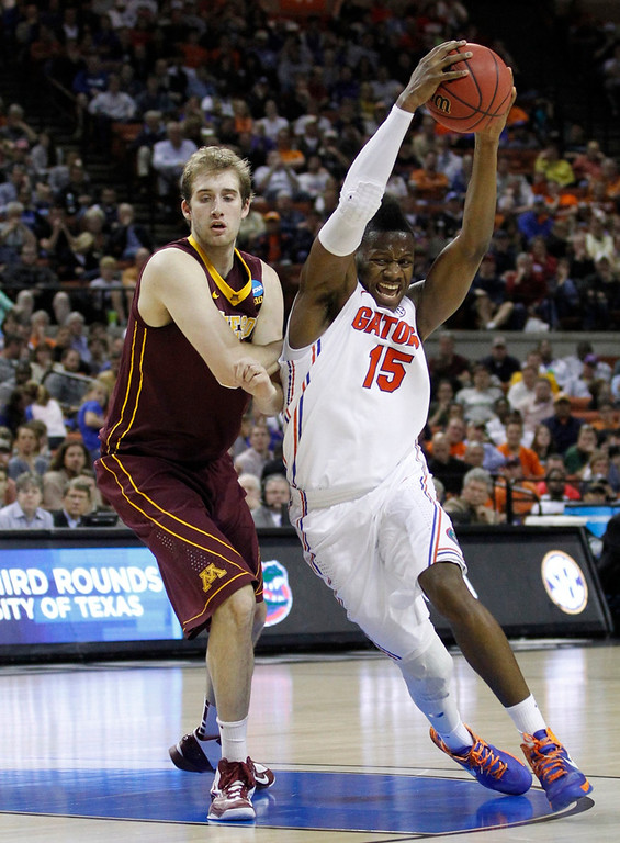 . University of Florida forward Will Yeguete (R) drives on University of Minnesota center Elliott Eliason during the first half of their third round NCAA basketball game in Austin, Texas March 24, 2013.  REUTERS/Mike Stone