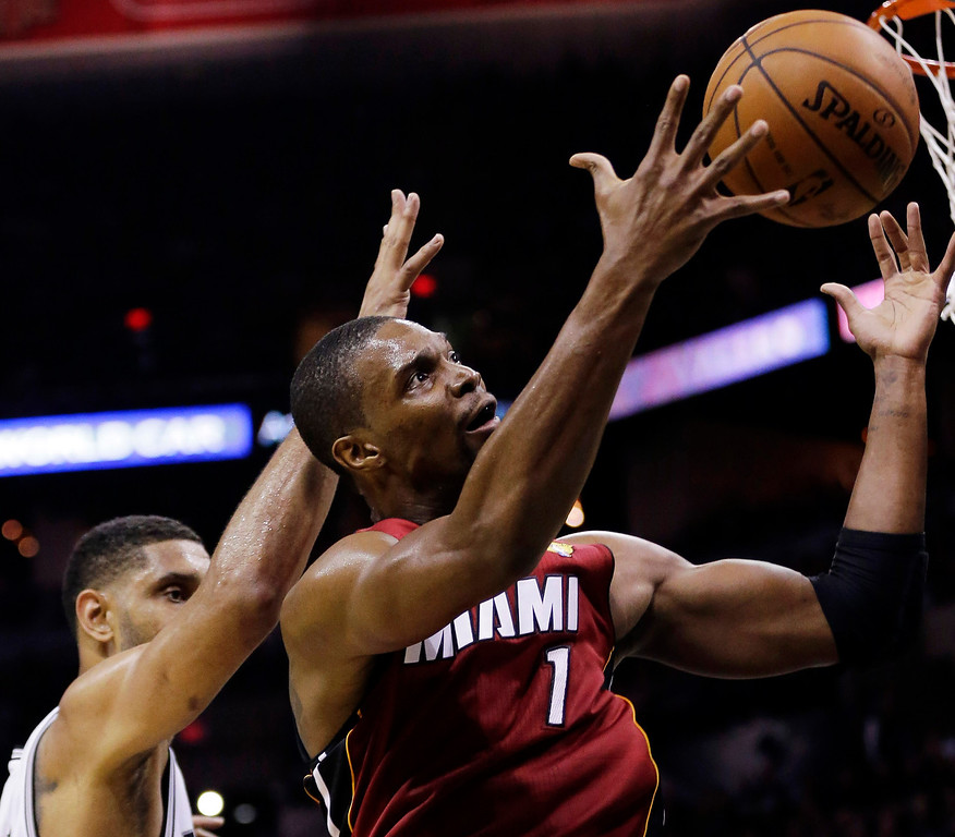 . Miami Heat center Chris Bosh (1) grabs a rebound as San Antonio Spurs forward Tim Duncan defends during the first half in Game 1 of the NBA basketball finals on Thursday, June 5, 2014, in San Antonio. (AP Photo/Eric Gay)