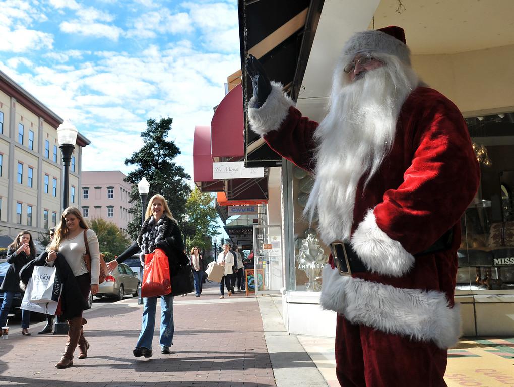 . Santa waves to shoppers as they pass 24e  Design Co.while Black Friday shopping Friday, Nov. 29, 2013 on Broughton Street in Savannah, Ga. (AP Photo/Savannah Morning News, Richard Burkhart)