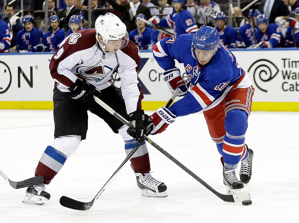 . New York Rangers\' John Moore, right, fights for control of the puck with Colorado Avalanche\'s Matt Duchene (9) during the first period of an NHL hockey game, Tuesday, Feb. 4, 2014, in New York. (AP Photo/Frank Franklin II)