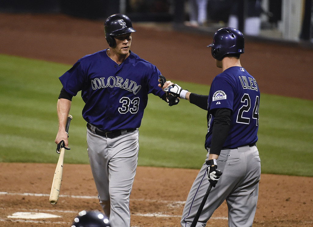 . Justin Morneau #33 of the Colorado Rockies, left, is congratulated by Jordan Lyles #24 after scoring during the fourth inning of a baseball game against the San Diego Padres at Petco Park April 14, 2014 in San Diego, California.  (Photo by Denis Poroy/Getty Images)