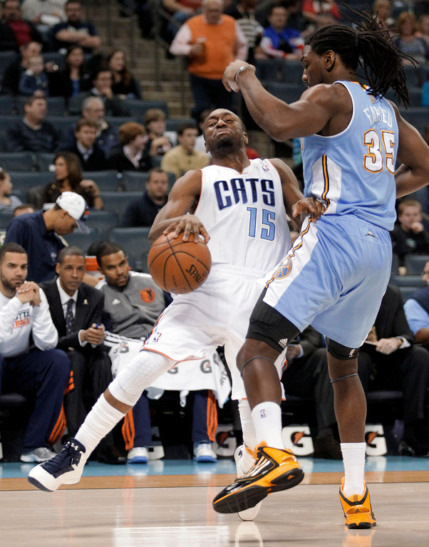 . Charlotte Bobcats\' Kemba Walker (15) grimaces and keeps the dribble as he gets fouled by Denver Nuggets\' Kenneth Faried (35) during the first half of an NBA basketball game in Charlotte, N.C., Saturday, Feb. 23, 2013. (AP Photo/Bob Leverone)
