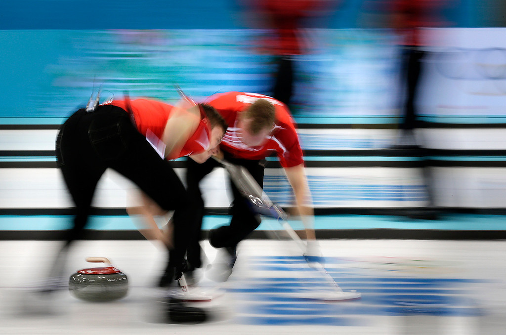 . Denmark\'s Troels Harry, left, and Mikkel Poulsen sweep the ice during the men\'s curling competition against Russia at the 2014 Winter Olympics, Monday, Feb. 10, 2014, in Sochi, Russia. (AP Photo/Wong Maye-E)