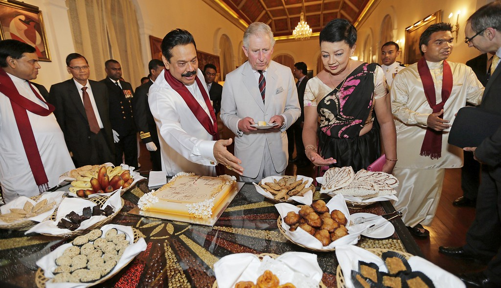 . In this handout photo provided by Sri Lankan Government, Sri Lankan President Mahinda Rajapaksa (L) shows Prince Charles, Prince of Wales (C) traditional food during a reception at the President\'s House on November 14, 2013 in Colombo, Sri Lanka. T  (Photo by Sri Lankan Government via Getty Images)